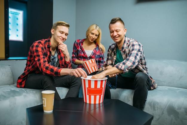 Przyjaciele jedzą popcorn w sali kinowej przed seansem. młodzieży płci męskiej i żeńskiej siedzi na kanapie w kinie