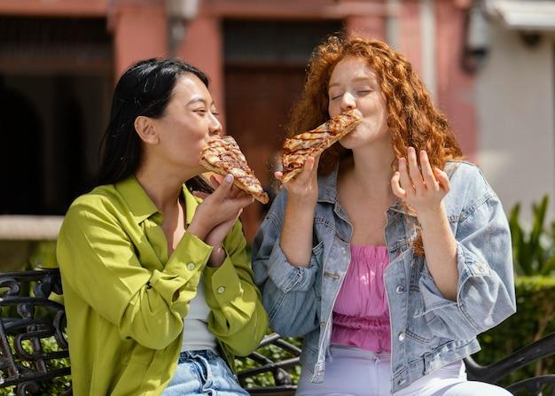 Przyjaciele jedzą razem uliczne jedzenie