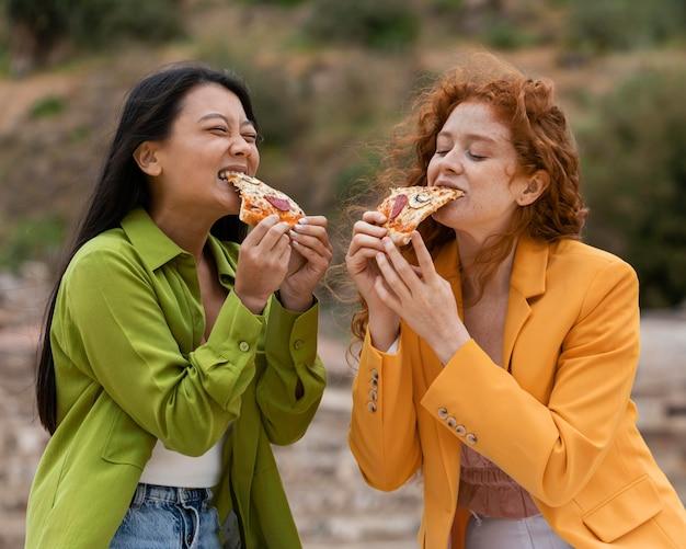 Przyjaciele jedzą uliczne jedzenie na świeżym powietrzu