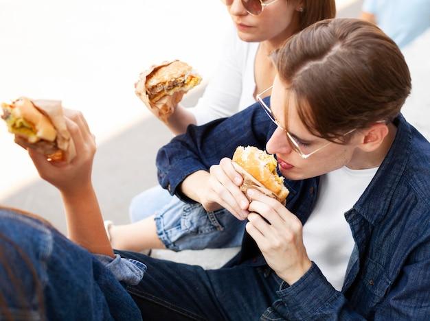 Przyjaciele jedzący hamburgery na świeżym powietrzu