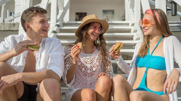 Przyjaciele jedzący hamburgery razem na świeżym powietrzu