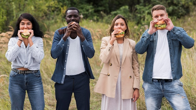 Przyjaciele jedzący hamburgery z przodu