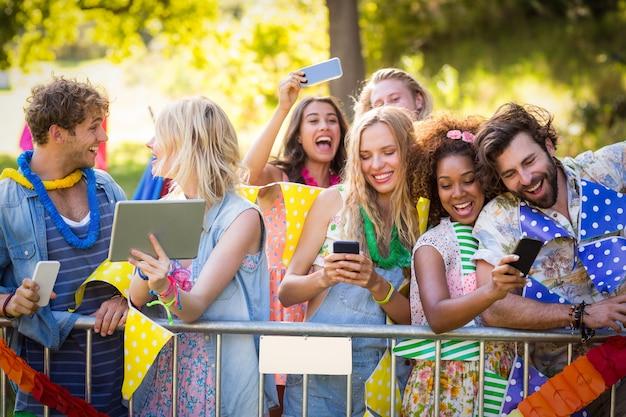 Przyjaciele klikają zdjęcia ze swoich telefonów komórkowych i tabletu cyfrowego