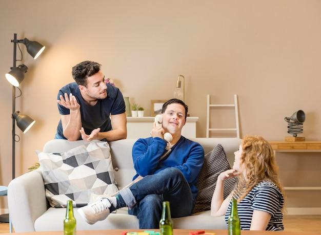 Przyjaciele kłócą się, podczas gdy mężczyzna rozmawia przez telefon