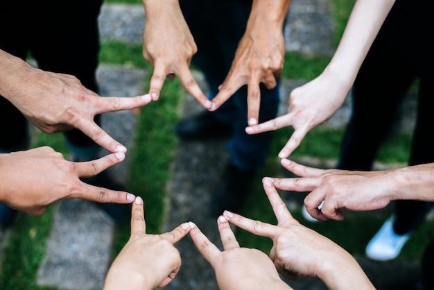 Przyjaciele kobiet i mężczyzn tworzą kształt gwiazdy z palców. sukces, koncepcja przyjaźni.