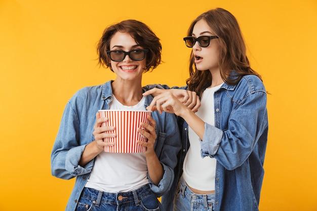 Przyjaciele kobiet na białym tle nad żółtą ścianą trzymając pop kukurydzy oglądać film.