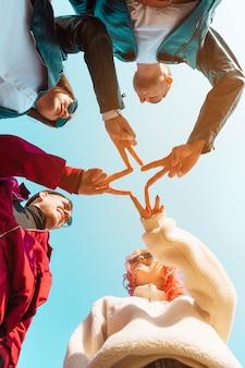 Przyjaciele łącząc ręce z gestem pokoju