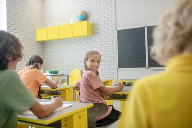 Przyjaciele. ładna dziewczyna siedzi przy biurku w klasie i uśmiecha się do swojego kolegi z klasy