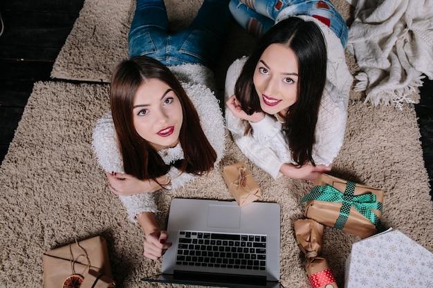 Przyjaciele leżącego na podłodze z laptopem i patrząc w górę