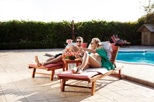 Przyjaciele leżący na leżakach w pobliżu basenu, robiąc selfie, uśmiechając się