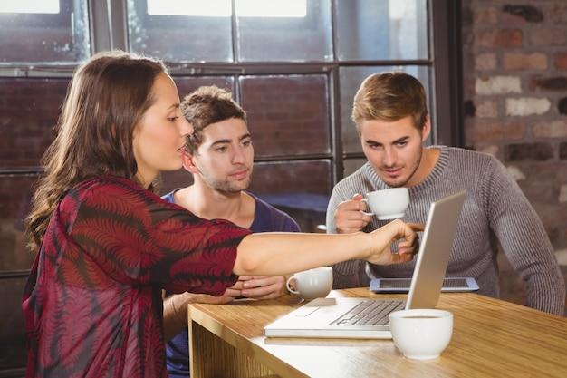 Przyjaciele ma kawę i używa laptop wpólnie