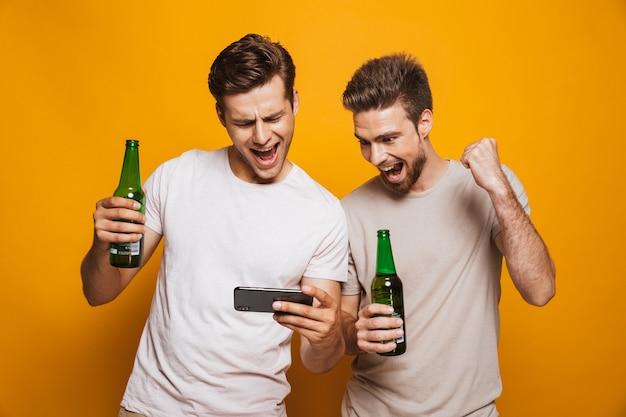 Przyjaciele mężczyzn korzystających z telefonu komórkowego wykonują gest zwycięzcy.