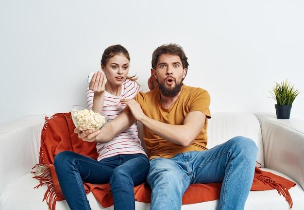 Przyjaciele mężczyzna i kobieta z popcornem na kanapie wnętrza.