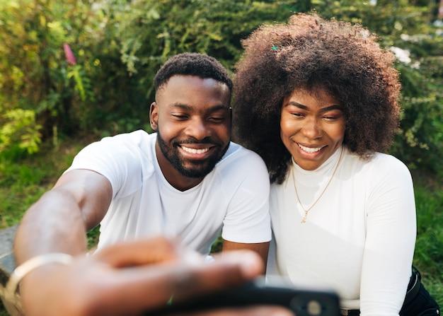 Przyjaciele międzykulturowi na zewnątrz przy selfie