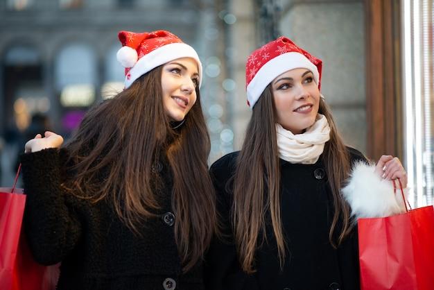 Przyjaciele młodych kobiet razem zakupy przed świętami bożego narodzenia