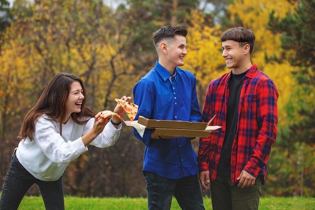 Przyjaciele młodzi, zabawni, piękni lubią pizzę i towarzysko na pikniku w naturze