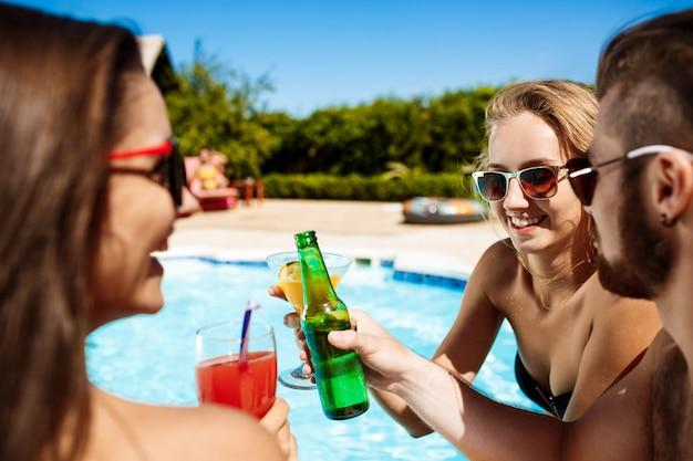 Przyjaciele mówią, uśmiechają się, piją koktajle, odpoczywają, relaksują się w pobliżu basenu
