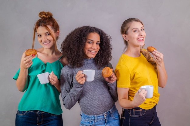 Przyjaciele na podwieczorku jedzą pączki i piją kawę z mlekiem