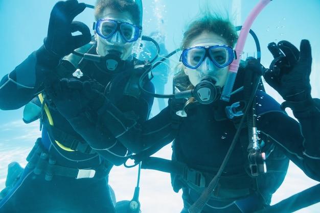 Przyjaciele na treningu nurkowania zanurzone w basenie patrząc na kamery