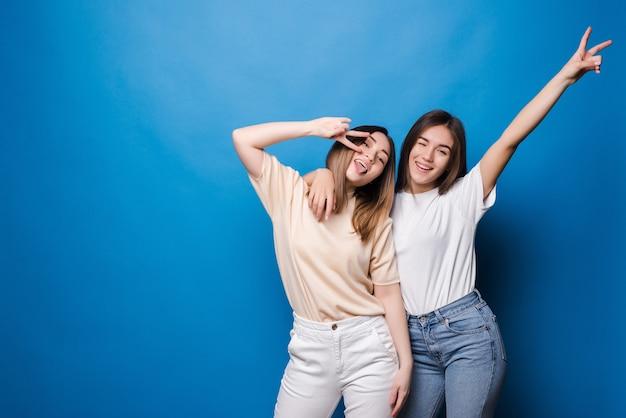 Przyjaciele na zawsze. dwie urocze dziewczyny przyjaciółki w okularach przeciwsłonecznych z uśmiechem na niebieskiej ścianie