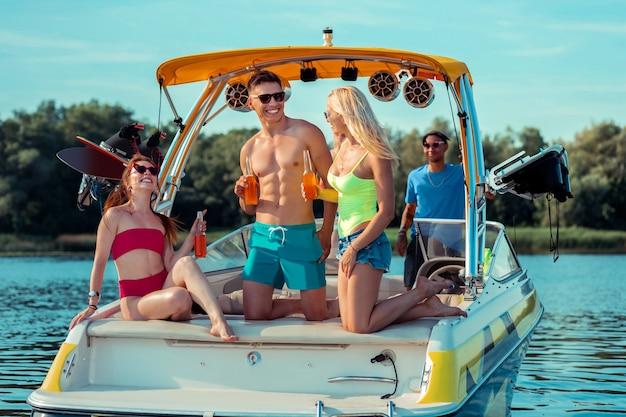 Przyjaciele na zawsze. zbliżenie na towarzystwo pełnych temperamentu przyjaciół siedzących na tylnym pokładzie jachtu, śmiejąc się i świętując