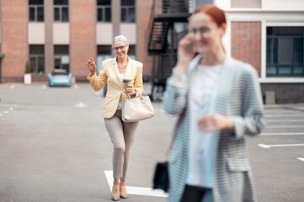 Przyjaciele na zewnątrz. uśmiechnięta stylowa starsza bizneswoman spotykająca się ze swoim młodym przyjacielem rozmawiająca przez telefon na zewnątrz