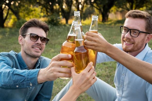 Przyjaciele na zewnątrz w parku piją razem piwo