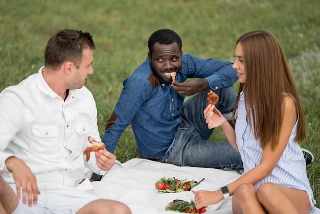 Przyjaciele na zewnątrz w przyrodzie jedzenie z grilla