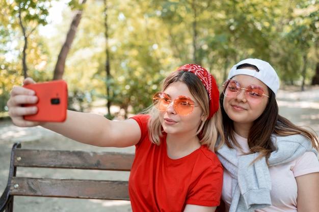 Przyjaciele nastolatki w okularach, biorąc selfie