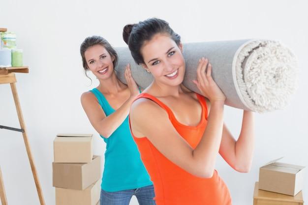 Przyjaciele niesie rolled dywanik po ruszać się w domu
