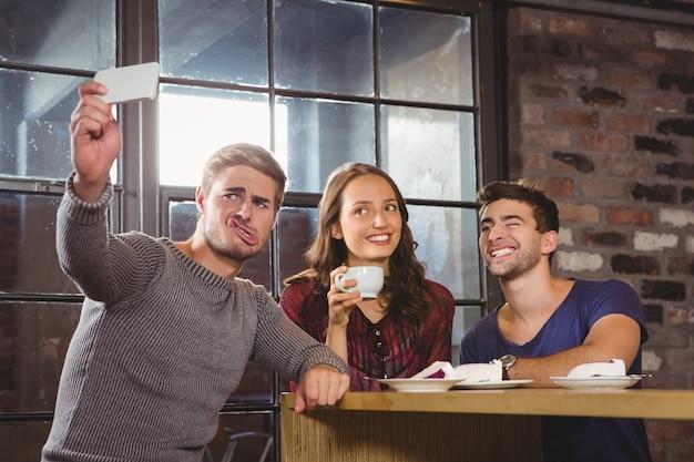 Przyjaciele o kawę i biorąc śmieszne selfie