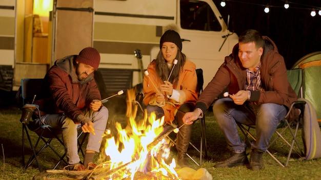 Przyjaciele odpoczywają przy ognisku i pieką pianki na patykach. retro samochód kempingowy. zimna noc.