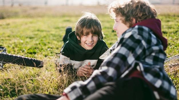 Przyjaciele odpoczywający na trawie podczas jazdy na rowerach