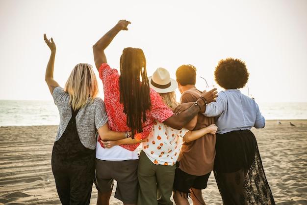 Przyjaciele ogląda zmierzch przy plażą
