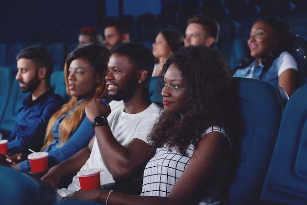Przyjaciele oglądają film w nowoczesnej sali kinowej