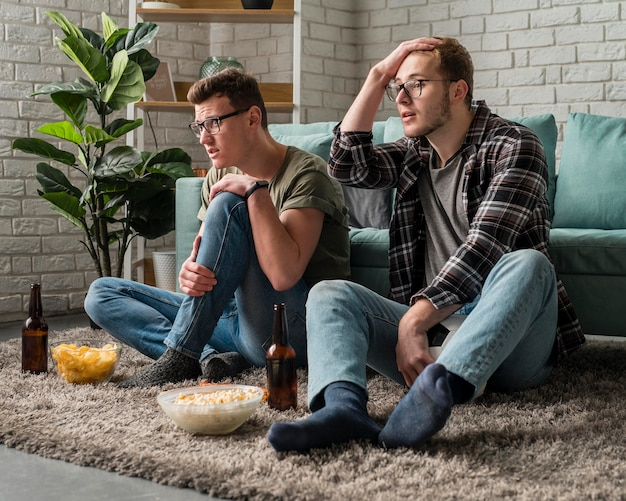 Przyjaciele oglądają razem sport w telewizji, jedząc przekąski i piwo