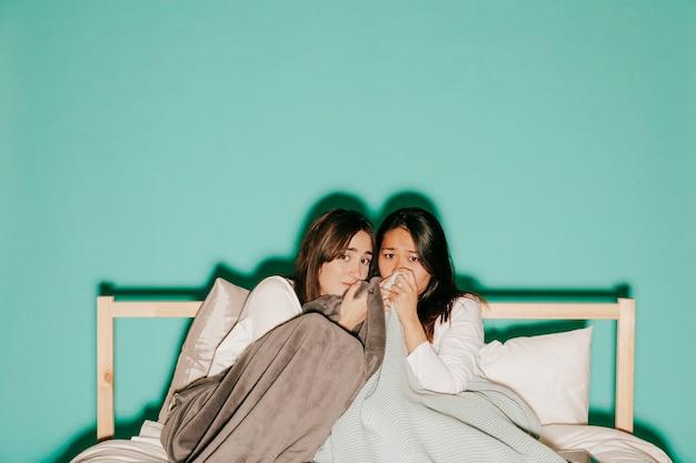 Przyjaciele oglądają straszny film w łóżku