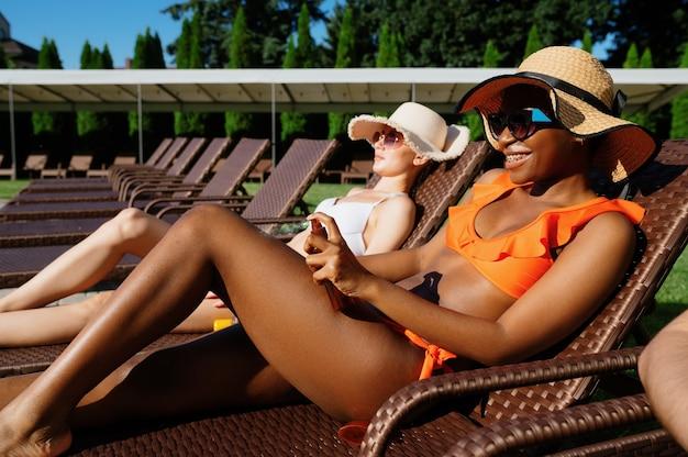 Przyjaciele opalają się na leżakach przy basenie. szczęśliwi ludzie bawią się na letnie wakacje, impreza świąteczna przy basenie na świeżym powietrzu. jeden mężczyzna i dwie kobiety wypoczywają w ośrodku?