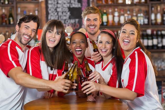 Przyjaciele opiekania butelek piwa w pubie