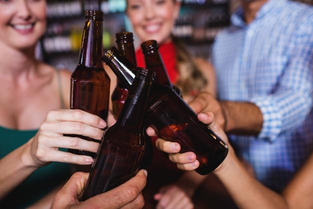 Przyjaciele opiekania butelkę piwa w klubie nocnym