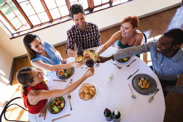 Przyjaciele opiekania kieliszek do wina przy stole w restauracji
