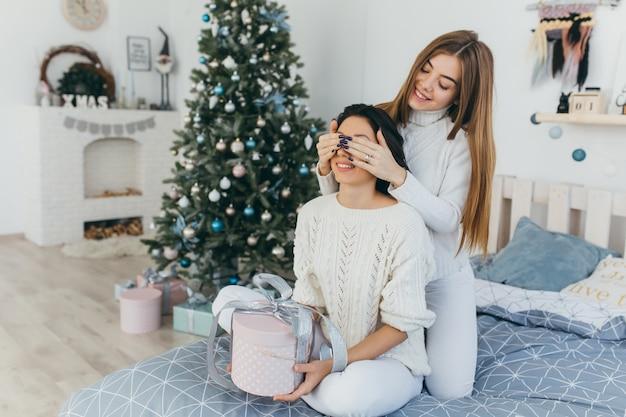 Przyjaciele otwierają prezenty świąteczne.