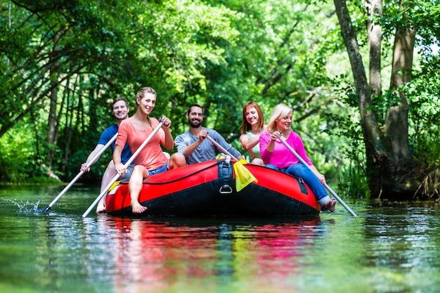 Przyjaciele paddling na gumowej łodzi przy lasową rzeką lub zatoczką