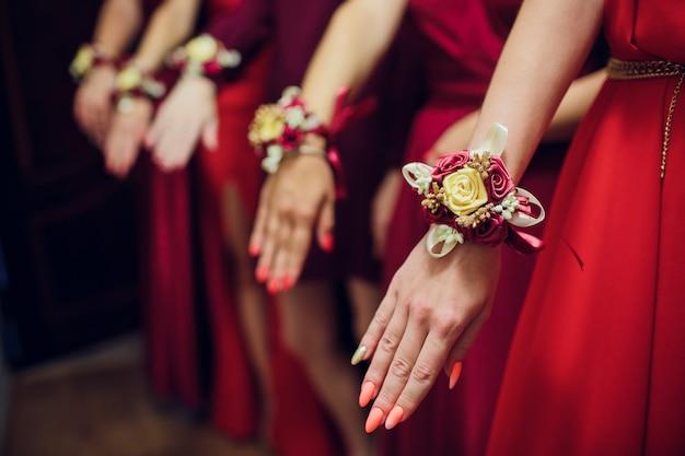 Przyjaciele panny młodej pokazują sobie manicure. zielone sukienki. koncepcja ślubu, przyjaźni i mody. kobiety pokazują manicure