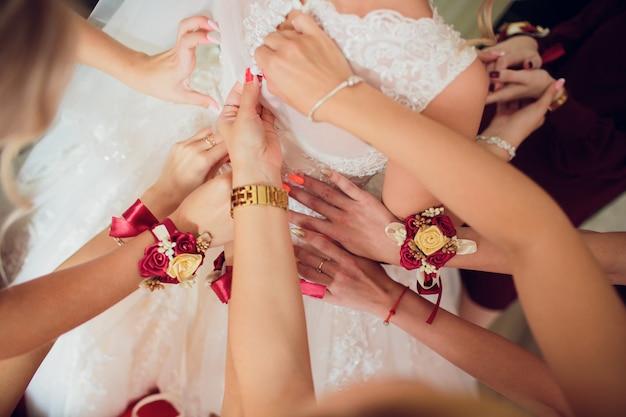 Przyjaciele panny młodej pokazują sobie manicure. zielone sukienki. koncepcja ślubu, przyjaźni i mody