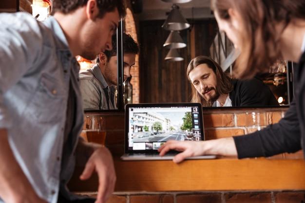 Przyjaciele patrząc na laptopa, nowa strona internetowa
