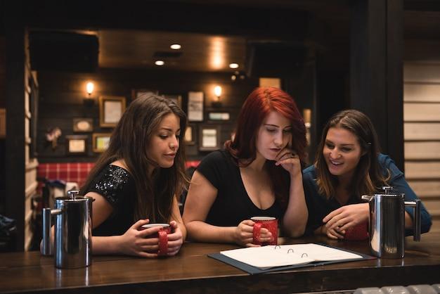 Przyjaciele patrząc na menu w barze