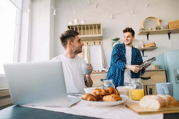 Przyjaciele patrząc na siebie trzymając magazyn i filiżankę kawy w kuchni