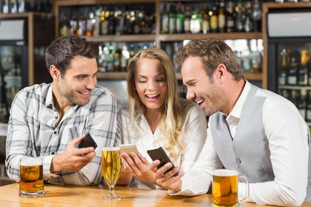 Przyjaciele patrząc na smartfony
