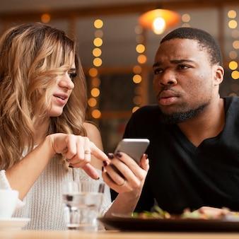 Przyjaciele patrząc na telefon komórkowy z makiety